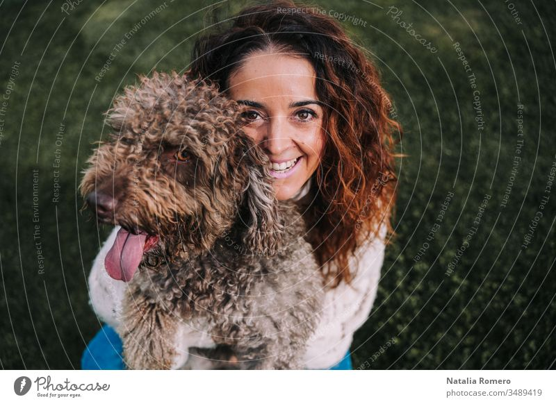 A beautiful woman is in the meadow with her dog. The owner is hugging her pet while she is looking at the camera. They are enjoying a day in the park. The pet is a Spanish water dog with brown fur.