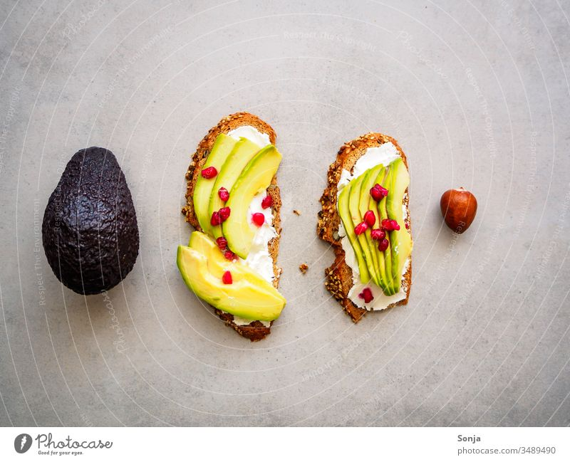 wholemeal bread with avocado and pomegranate seeds, one whole avocado and one seed on a grey background, top view, healthy breakfast Avocado Slice