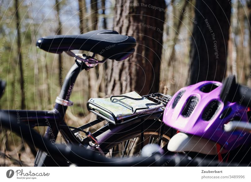 Saddle of a bicycle with map and bicycle helmet during a bicycle tour in the forest Bicycle bike tour Wheel Bike helmet Map luggage carrier Forest trees purple