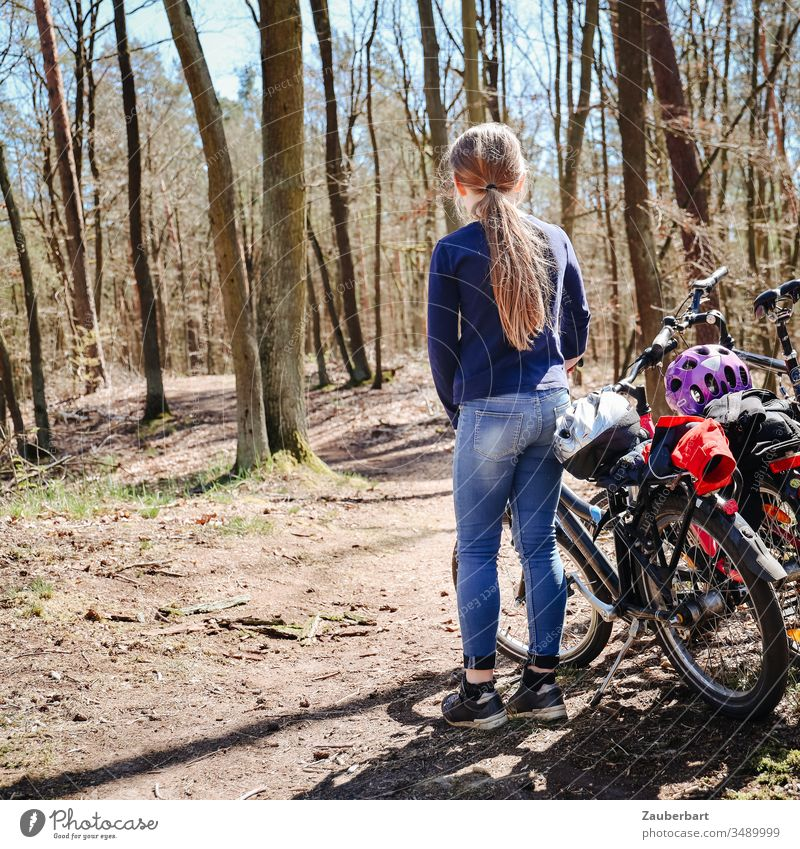 Child with bicycle stands on a forest path during a bicycle tour Girl Bicycle bike tour Forest trees jeans Ponytail Sun Infancy Family