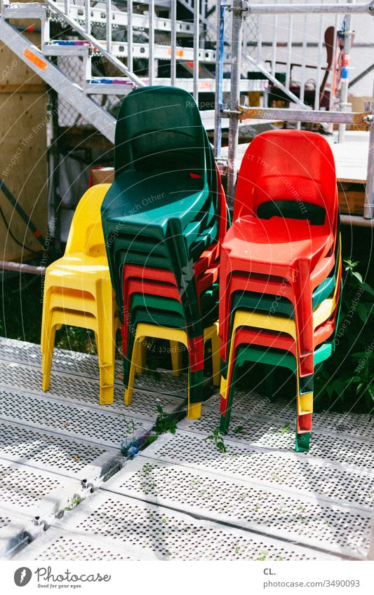 a stack of coloured chairs Chair variegated Stack stackable out Event Plastic chair plastic event Red Yellow Green Colour photo Deserted Exterior shot Day