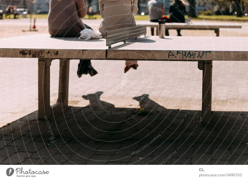 people sitting on table tennis tables Table tennis table Sit Break take a break Playground Lunch hour Park persons Relaxation Exterior shot Day Colour photo
