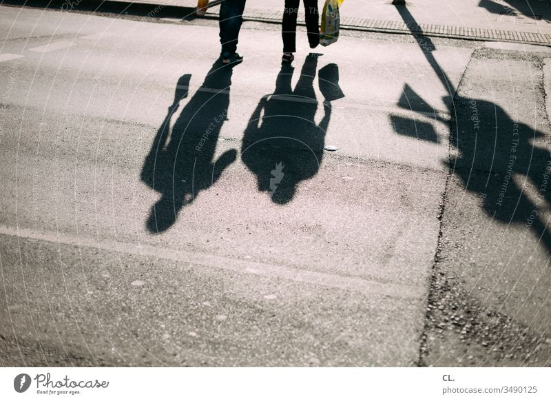 shadows of two people in the street Pedestrian Going Couple Movement Shadow Street Shadow play To go for a walk take a walk Shopping Shopping Bags