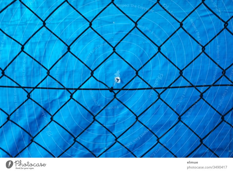 Mesh wire fence in front of blue PVC tarpaulin with small hole Wire netting fence Screening Protection demarcation Hollow Peephole Fence Boundary Border Blue