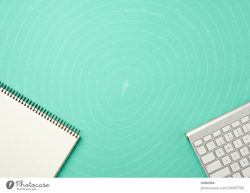 white wireless aluminum keyboard and open notebook with blank white sheets on a green background desktop tech business pc computer modern laptop office