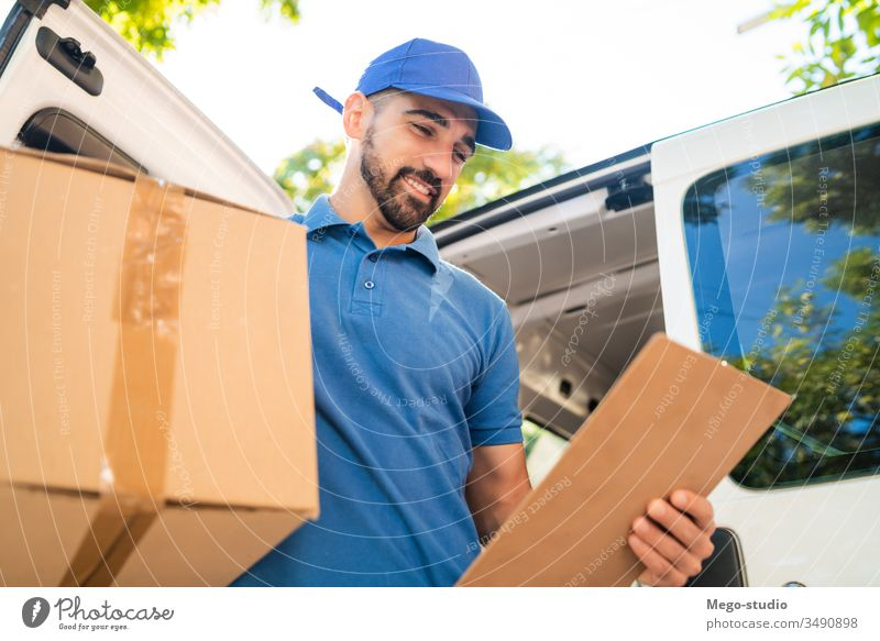 Delivery man unloading cardboard boxes from van. male service package delivery shipping industry work send office closeup logistic consumer carrying profession