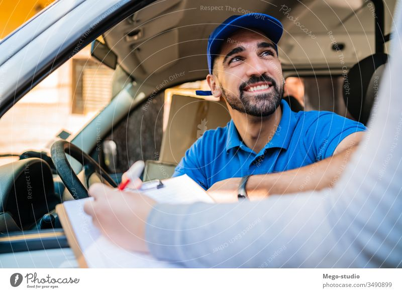 Delivery man in van while customer sign in clipboard. male service package delivery shipping industry work send office closeup logistic consumer carrying