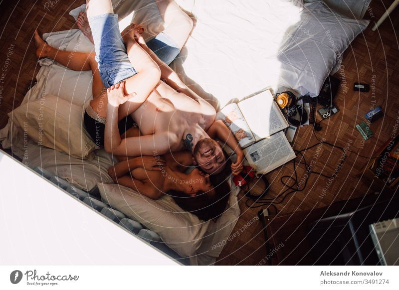 Young funny couple laughs lie on a floor with pillows and vintage books and headphones laughing headpones mc nude anatomy sunlight shadow Youth (Young adults)