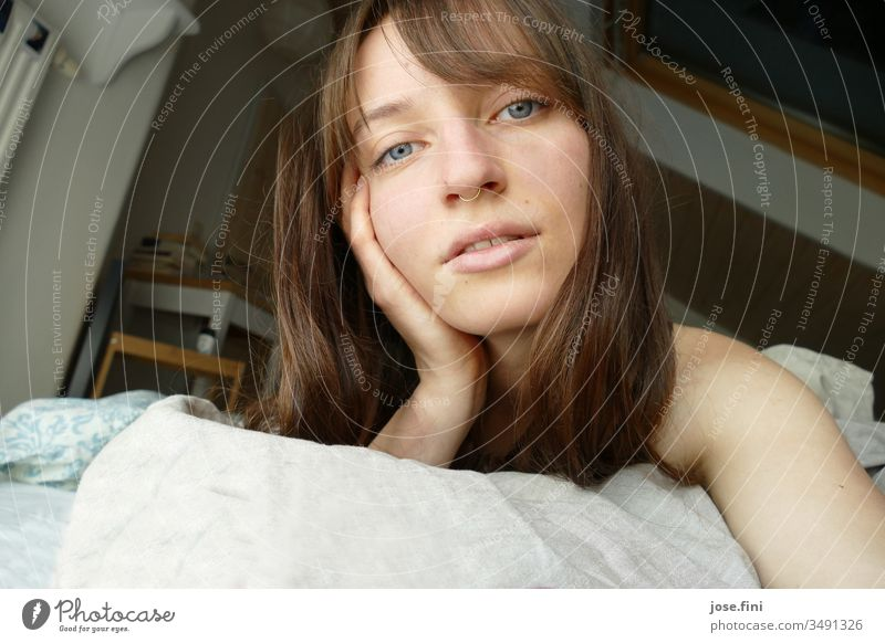 Portrait of a young woman lying in bed in the morning Long-haired Joie de vivre (Vitality) Simple Young woman fringe hairstyle Looking into the camera pretty