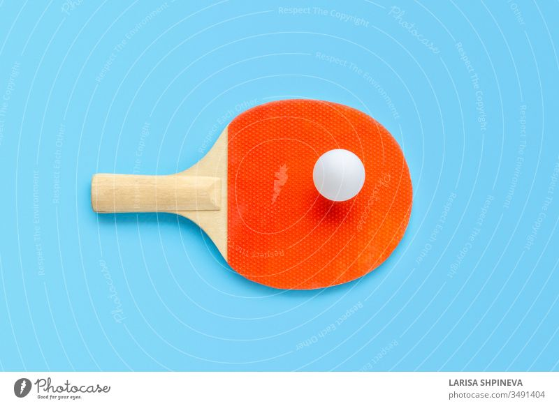 Red racket for table tennis with white ball on blue background. Ping pong sports equipment in minimal style. Flat lay, top view, copy space ping handle game