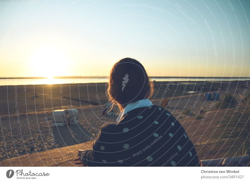 Young woman sits with her back to the camera on the beach promenade and looks over the beach into the sunset over the North Sea Beach Sit Ocean