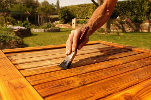 Glaze painting woodwork outdoors in spring. Spring works. Spring has come. Male hand with a brush. Renovation work, carpentry details with woodwork and craftsmen. Time to work outside.