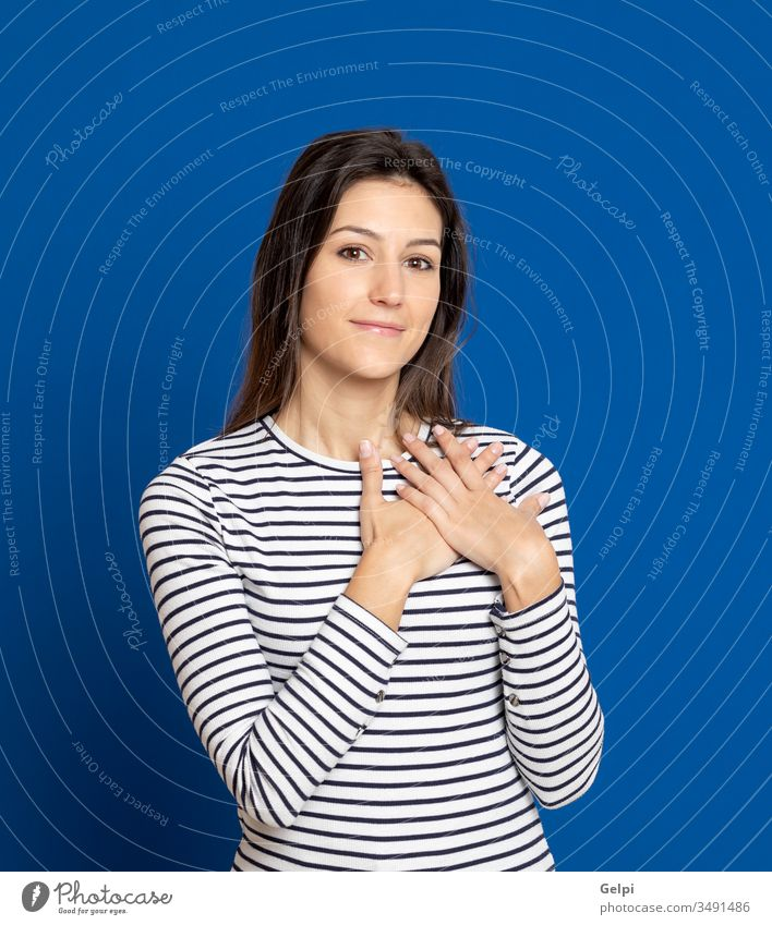 Brunette young woman wearing a striped T-shirt girl person love feel hand together in love romantic happy smile faith heart inspired blue expression gesture
