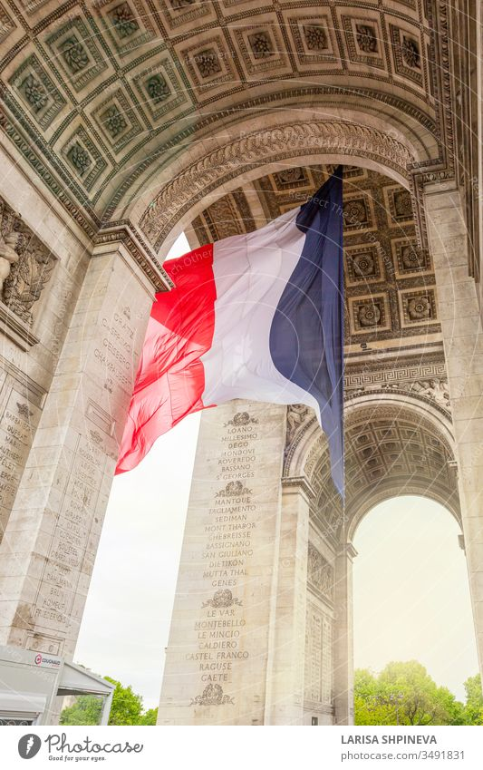View of Arc de Triomp with flag of France waving in wind on Place de Gaulle in Paris, France paris arch triomphe france monument europe city charles gaulle