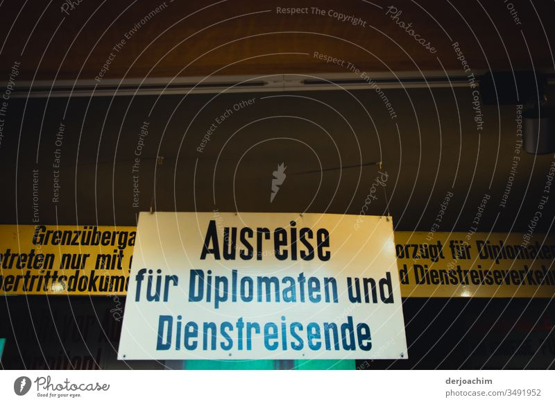 A large in white held sign / exit for diplomats and Diestreisende / border crossing GDR - Germany Berlin. Architecture Modern Clue Sky High-rise Day Glass
