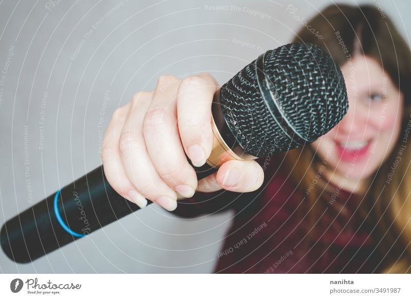 Young woman singing with a microphone loud techonology sound art artist concept leisure activity active blonde casual real people hobby trendy voice black