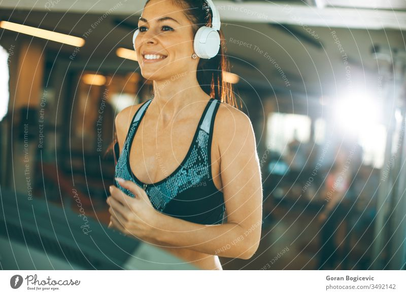 Young woman running on treadmill during sports training in a gym fit fitness female athlete exercise health sportswear workout healthy machine attractive young