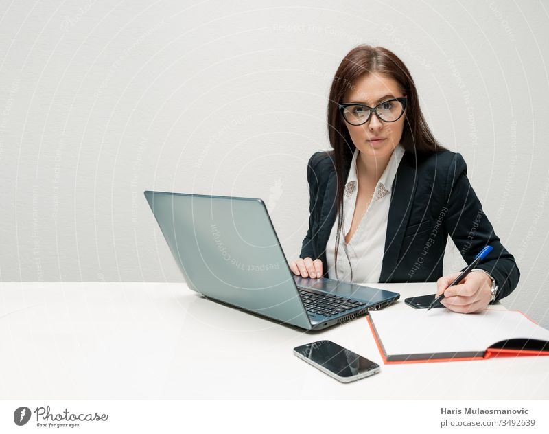 Businesswoman working in office with attitude looking at the camera  with laptop and mobile phone agent ambitious assistant attractive beautiful business