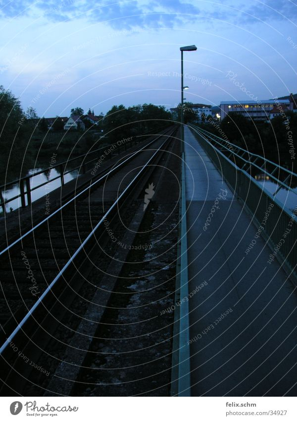 Double-track Railroad tracks Sidewalk Lantern Street lighting Junction Parallel Side by side Evening sun Twilight Horizon Bridge River branch Water Handrail