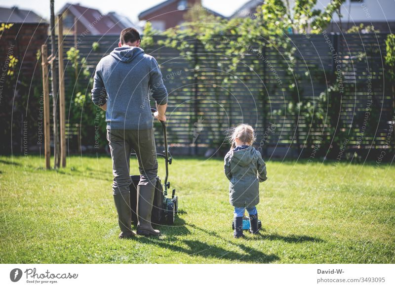 Family - father and daughter mow the lawn in the garden Child Infancy Father Daughter Man Girl Garden Mow the lawn Lawn Lawnmower Gardening Copy Space right