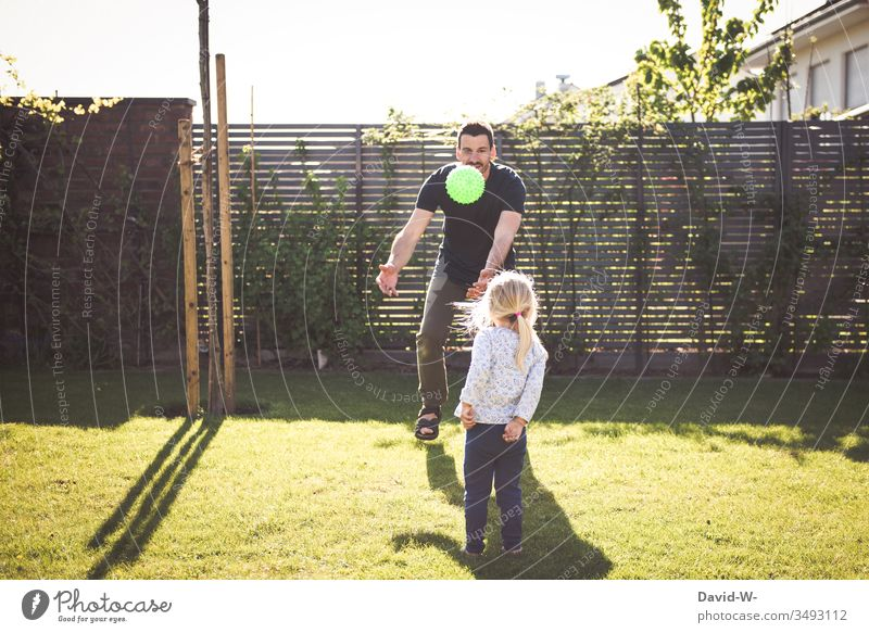 Child and father play in the garden with a ball throwing and catching Girl Man Daughter Father Playing Ball Throw Catch Garden occupy fun Laughter Joy Flying