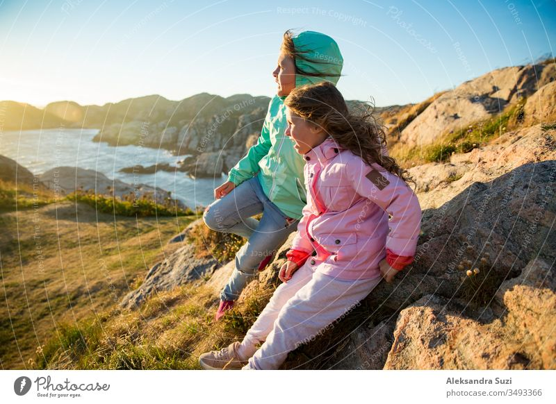 Two little girls play on rocky northern seashore. Sit, laugh, hug, explore the coastal rocks. Travel and enjoy a great adventure in Norway. Beautiful view of fjord and mountains in sunset.