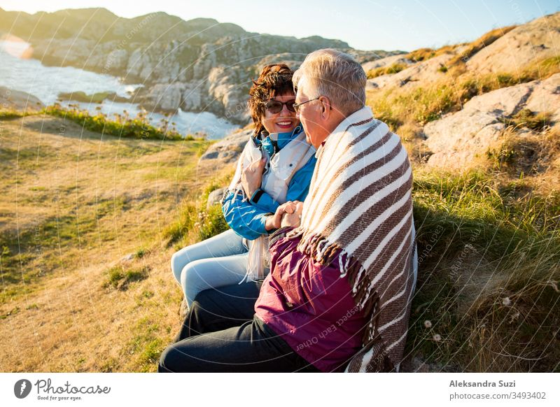 Loving mature couple hiking, sitting on windy top of rock, exploring. Active Mature man and woman wrapped in blanket, hugging and Happily smiling. Scenic view of sea, mountains. Norway, Lindesnes.