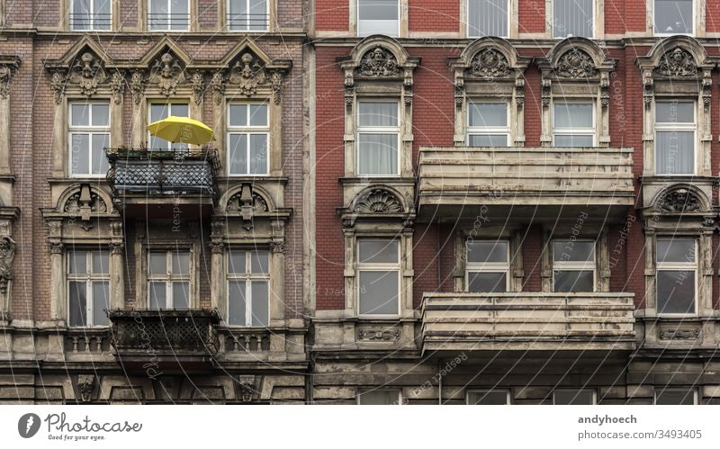 The yellow parasol on the balcony of the old house ancient antique apartment arch architecture balconies Berlin brick wall building building exterior