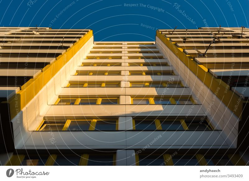 An apartment building with yellow windows in the morning light architecture balconies balcony Berlin block blue blue sky building exterior built structure