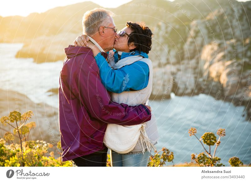 Loving mature couple traveling, standing on the top of rock, exploring. Active man and woman hugging and kissing, Happily smiling. Scenic view of mountains and sea on sunset. Norway, Lindesnes