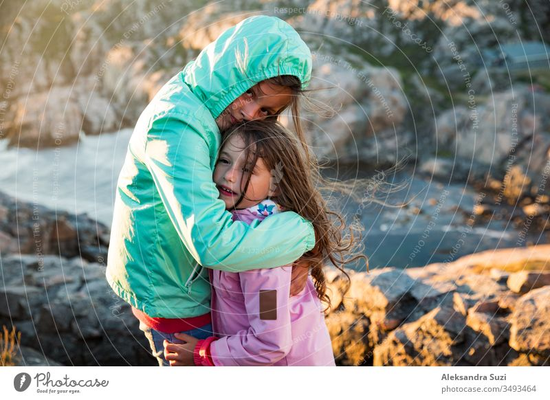 Two little girls play on rocky northern seashore. stand, laugh, hug, explore the coastal rocks. Travel and enjoy a great adventure in Norway. Beautiful view of fjord and mountains in sunset.