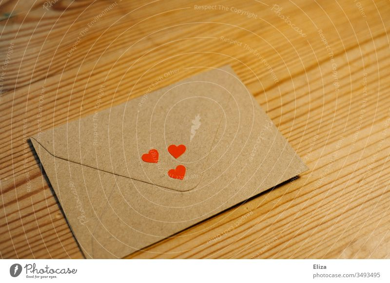 An envelope with three little red hearts on a brown wooden table; concept love, love letter Envelope (Mail) Letter (Mail) Love letter cuddle Greetings Heart Red