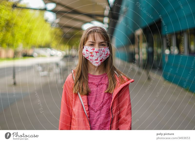 Young girl with a pretty self-sewn mouth-nose-mask, which has flamingos as a pattern on it, biological danger by coronavirus: Covid-19-danger person Epidemic