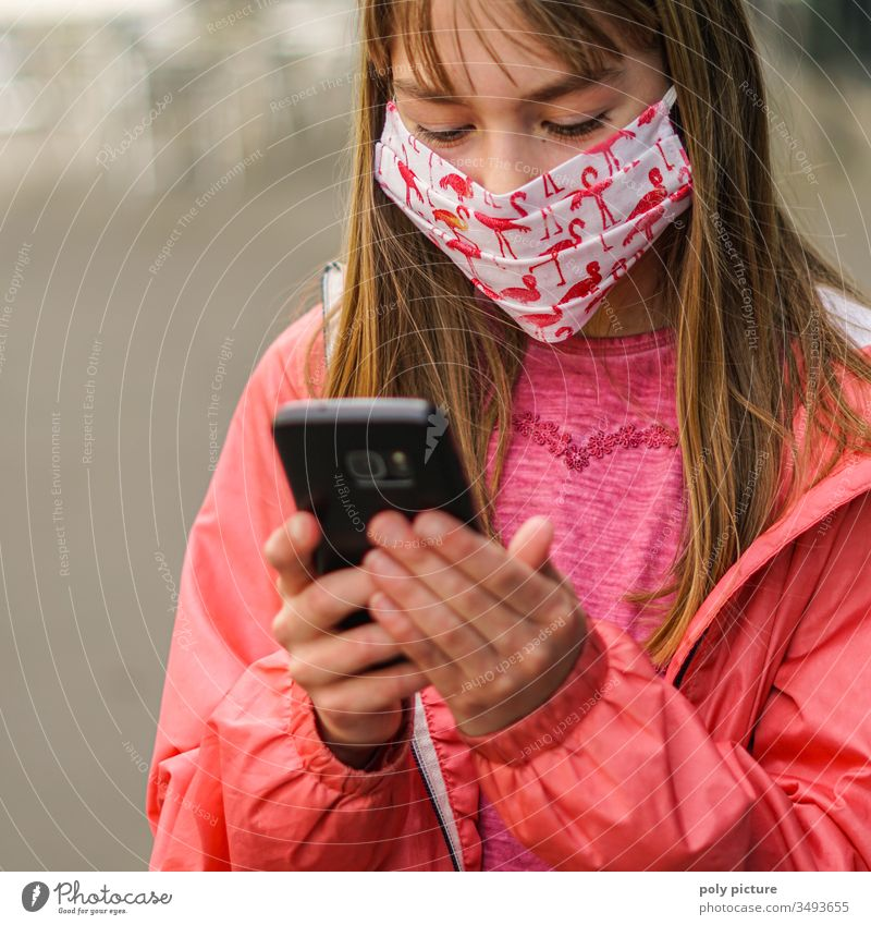 young girl with a mouth-nose-mask and smartphone in her hand, biological danger from coronavirus: Covid-19 danger Epidemic Protection Virus flu Allergy Illness