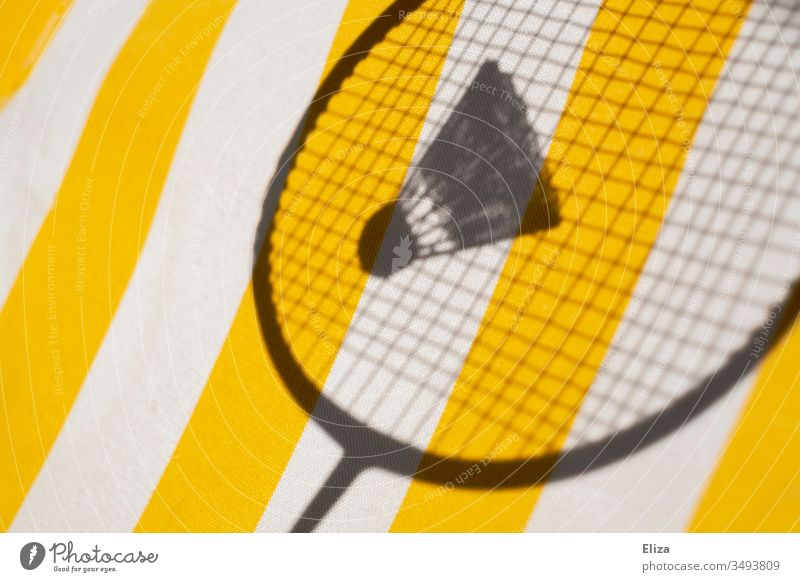 The shadow of a badminton racket with a shuttlecock in front of a striped yellow background; badminton Shuttlecock Badminton badminton rackets Badminton racket