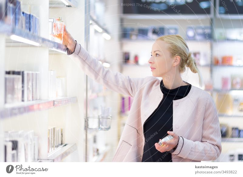 Beautiful woman shopping in beauty store. shopper buy cosmetics market drugstore fragrance tester perfume scent adult shelf casual boutique female girl choosing