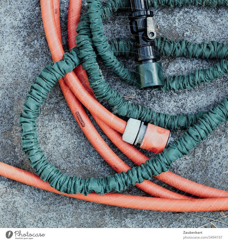 A red and a green garden hose in a delicate wrap consider a closer connection Garden hose Hose Cast Red Green Connection connector Water Irrigation Gardening
