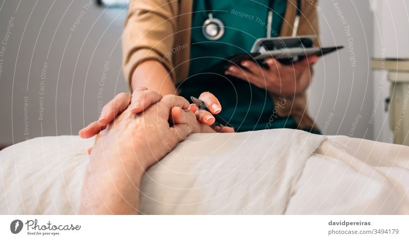 Female doctor comforting older patient unrecognizable hands coronavirus covid-19 death medical reassure loving hospital senior mortality rate decease