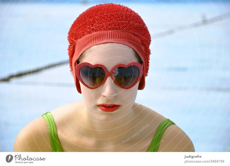 The girl with the beautiful red bathing cap and the green swimsuit looks through heart-shaped sunglasses directly into the camera. A summer love. Girl Woman