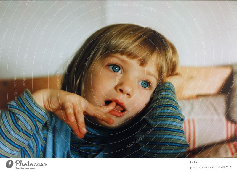 Little, sweet girl in a striped shirt, sitting on a wooden bench at the table at home and dreaming blue-eyedly into the air, sticking her index finger in her open mouth.