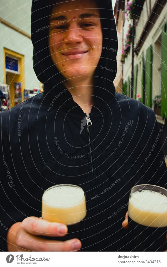 Young man holds two glasses with dark beer on the street ( smoked beer ) in his hand and smiles. The white foam in the glasses is well recognizable on his dark jacket.