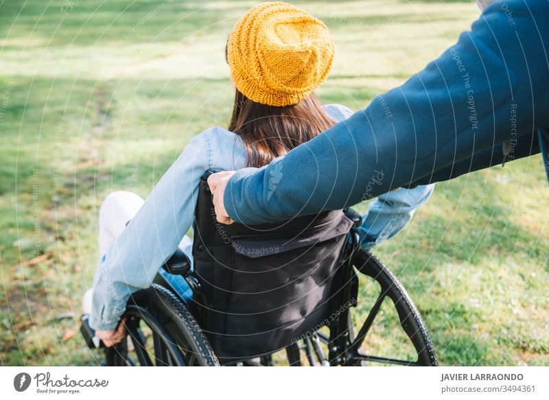Volunteer pushes the wheelchair of a young disabled girl in a ga accessibility disability woman volunteer happiness optimism mobility handicapped activity