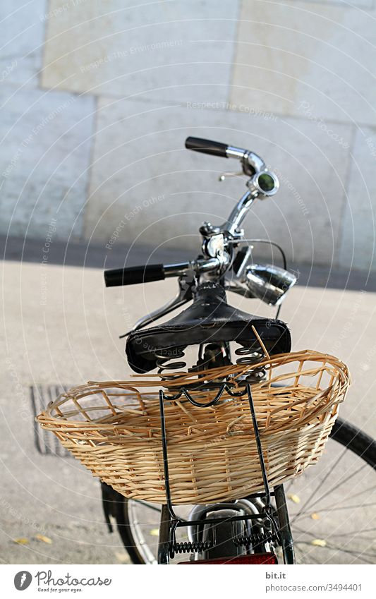 Bicycle with handlebars, saddle and basket for shopping and transport on the luggage rack is parked on the street, in the city, in front of a gray wall in the background.