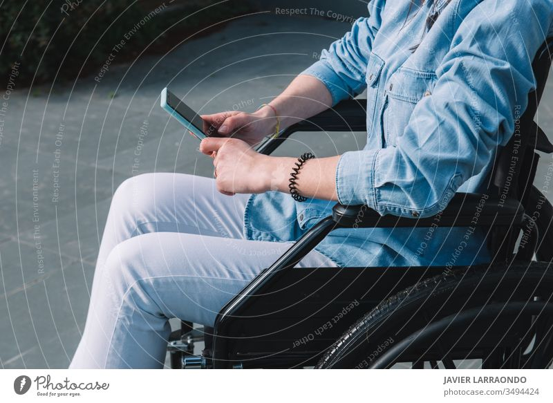 Disabled girl in a wheelchair using her mobile phone communication disabled smart phone casual lifestyle independence technology mobility accessibility