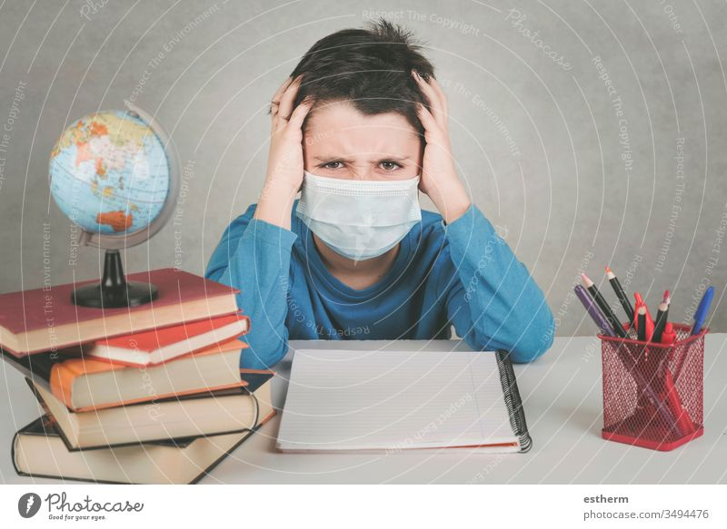 angry child wearing medical mask fed up with doing homework in the quarantine coronavirus epidemic pandemic stay home covid-19 student reading book education