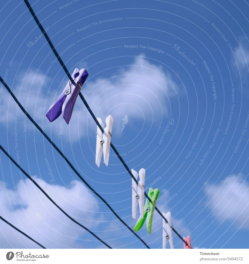 Clothes pegs enjoy the nice weather Clothesline Dry Plastic hang colors Sky Clouds Deserted Beautiful weather Blue White Denmark Exterior shot