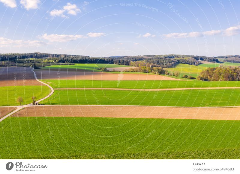 an agricultural landscape in the spring agricultural way tractor tractor path field background meadow background from above air aerial view aerial photo texture