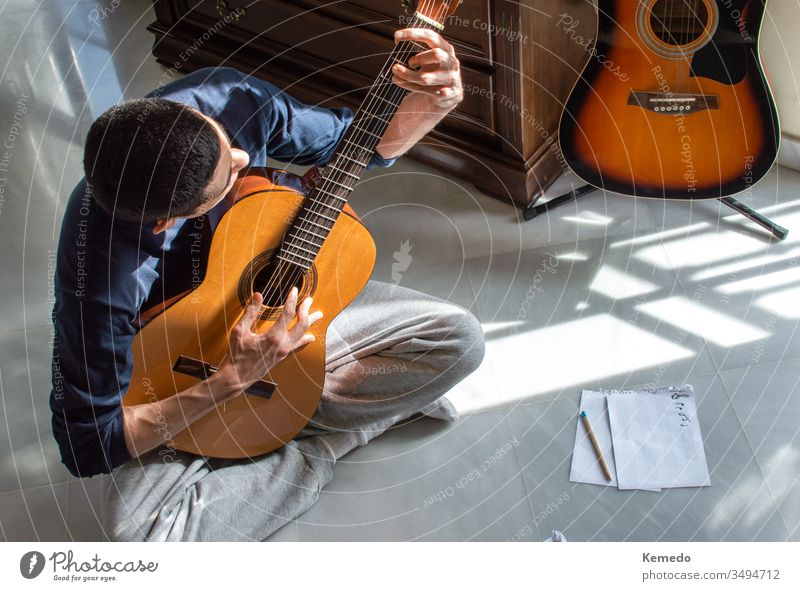 Man playing guitar and composing music at home near a bright window on a sunny day. Casual musician sitting on the floor playing the guitar. man compose