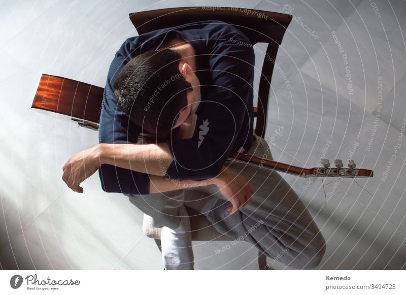 Bored and uninspired young take a break from playing the guitar. Top view of a man resting with a guitar. Concept of lack of inspiration or motivation. idea