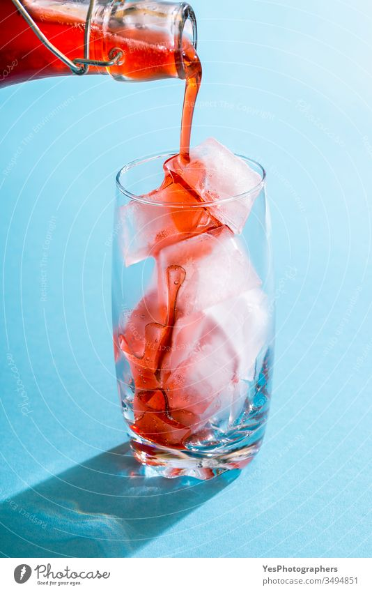Strawberry syrup pouring over ice cubes in a glass beverage blue bright close-up cocktail cold cold drink colorful copy space crystal clear delicious detox